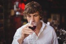 Hombre tomando una copa de vino tinto en el bar - foto de stock