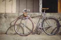 Bicicleta inclinada contra la pared en día soleado - foto de stock