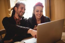 Smiling hipster couple using laptop while sitting at table — Stock Photo