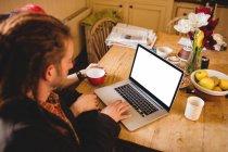 Pareja usando el ordenador portátil mientras está sentado en la mesa del desayuno - foto de stock