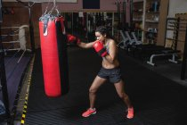 Вид збоку жіночий боксер практикуючих бокс з боксерської груші в фітнес-студія — стокове фото