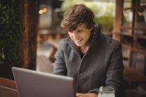Человек с ноутбуком в баре — стоковое фото