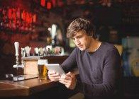 Человек, использующий цифровой планшет на барной стойке в баре — стоковое фото