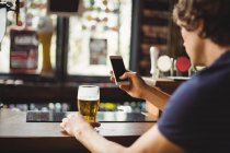Uomo che utilizza il telefono cellulare con un bicchiere di birra in mano al bar — Foto stock