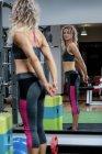 Красивая женщина выполняет упражнения на растяжку в тренажерном зале — стоковое фото