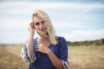 Portrait of attractive blonde woman standing in field — Stock Photo