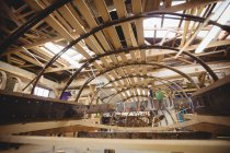 Wooden boat under construction in boatyard interior — Stock Photo