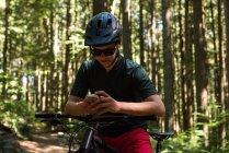 Homme cycliste utilisant un téléphone portable en forêt au soleil — Photo de stock