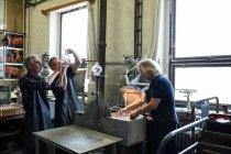 Стеклодувы рассматривают изделия из стекла на стеклодувном заводе — стоковое фото