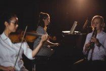 Tre studentesse che suonano pianoforte, clarinetto e violino in uno studio — Foto stock