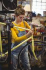 Mechanic repairing a bicycle handle bar in bicycle workshop — Stock Photo