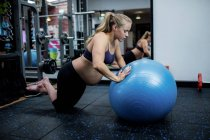 Pregnant woman exercising with fitness ball in gym — Stock Photo