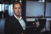 Ritratto di uomo d'affari seduto in ufficio con un bicchiere d'acqua e tablet digitale — Foto stock