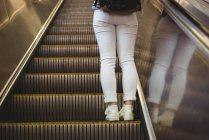 Sección baja de la mujer de pie en la escalera mecánica - foto de stock