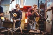 Équipe de souffleurs de verre façonnant un verre sur les pipes à l'usine de soufflage de verre — Photo de stock