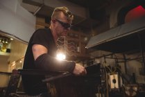 Glassblower forming and shaping molten glass at glassblowing factory — Stock Photo