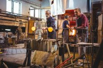Team of glassblowers shaping a glass on the blowpipes at glassblowing factory — Stock Photo
