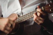 Mittelteil einer Frau, die in der Musikschule Gitarre spielt — Stockfoto