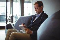 Uomo d'affari seduto sul divano con computer portatile e scrivere note nel diario in ufficio — Foto stock