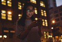Jovem mulher usando telefone celular na cidade à noite — Fotografia de Stock