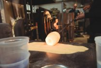Glassblower rolling molten glass over blowpipe glass on table at glassblowing factory — Stock Photo