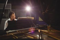 Female student playing piano in a studio — Stock Photo
