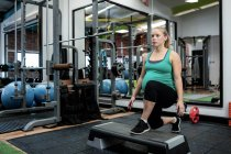 Pregnant woman performing exercise in gym — Stock Photo