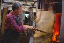 Glassblower heating glass in furnace at glassblowing factory — Stock Photo