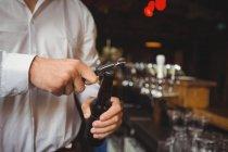 Sezione media del barista che apre una bottiglia di birra al bancone del bar — Foto stock