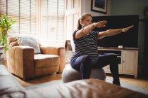 Foco seletivo da mulher grávida, realizando exercícios de alongamento na esfera da aptidão na sala de estar em casa — Fotografia de Stock