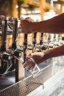 Крупный план заполнения бара тендером пива из барного насоса на стойке бара — стоковое фото