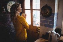 Frau schaut durch Fenster, während sie zu Hause in der Küche Kaffee trinkt — Stockfoto