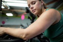 Portrait of pregnant woman working out on exercise bike at gym — Stock Photo