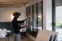 Боковой вид бизнесмена с помощью гарнитуры виртуальной реальности в офисе — стоковое фото