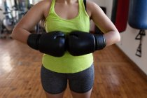 Mid section of female boxer standing with boxing gloves in fitness studio — Stock Photo