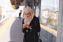 Hijab mulher usando telefone celular na plataforma na estação — Fotografia de Stock