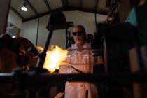 Рабочий мужчина с помощью сварочной горелки на стекольном заводе — стоковое фото