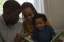 Eltern lesen mit ihrem Sohn zu Hause im Wohnzimmer ein Bilderbuch — Stockfoto