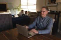 Uomo anziano che utilizza il computer portatile sul tavolo in soggiorno a casa — Foto stock