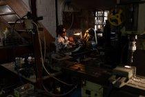 Arbeiterin mit Schweißbrenner in Glasfabrik — Stockfoto