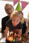 Cute girl blowing birthday candle at home — Stock Photo