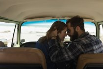 Romantic couple embracing in vehicle on roadtrip — Stock Photo