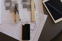 Planta, bússola, celular e tablet digital sobre uma mesa no escritório — Fotografia de Stock