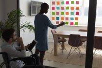 Dirigenti che lavorano su note adesive in ufficio — Foto stock