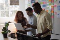 Руководители обсуждают за ноутбуком в офисе — стоковое фото