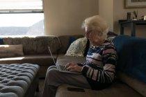 Пожилая женщина использует ноутбук в гостиной дома — стоковое фото