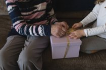 Mid section of grandmother and granddaughter opening gift box at home — Stock Photo
