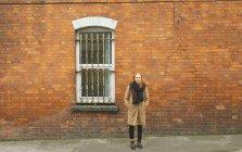 Mulher ruiva em pé com a mão no bolso, contra a parede de tijolos — Fotografia de Stock