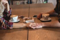 Romantic couple holding hand in cafe — Stock Photo