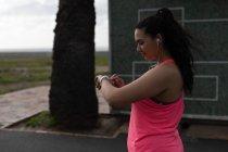 Vista lateral del corredor femenino usando reloj inteligente - foto de stock